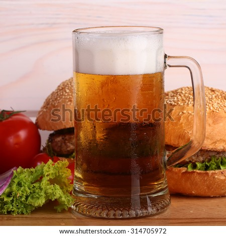 Few fresh tasty burgers of green lettuce meat cutlet tomato and white bun with sesame seeds near and glass of light beer with froth on octoberfest holiday on wooden background, square picture - stock photo