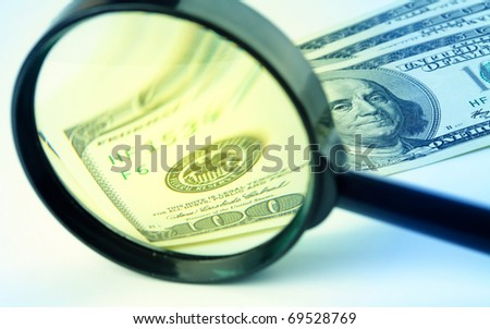 Few hundred dollars under a magnifying glass - stock photo