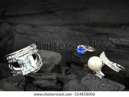 Few jewelry rings with brilliants, gems and pearl on black coal background, soft focus - stock photo