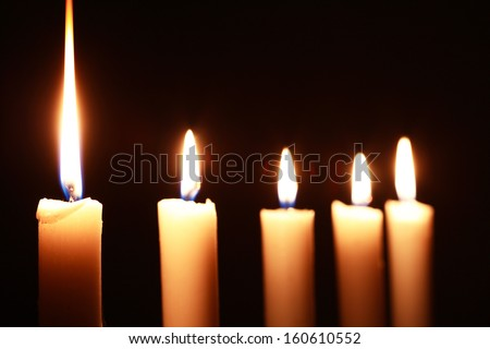 Few lighting candles in a row on dark background - stock photo