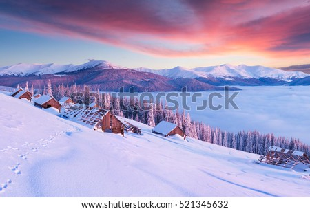 Few minutes before sunrise in abandoned Carpathian village. Colorful winter morning in the mountains. Artistic style post processed photo.