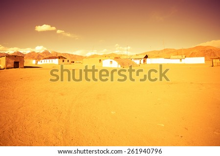 Few old houses, rocky mountains and scorched valley on a background of blue sky with a few white clouds.  Toned - stock photo