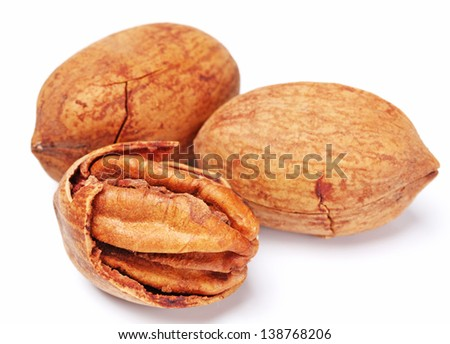 Few pecan nuts isolated on white, one cracked