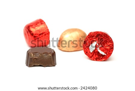 Few pieces of fancy chocolates,one of them with a bite missing, over white background.