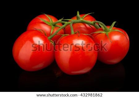 Few tomatoes isolated on black - stock photo