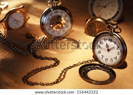 Few watches on sand background with light beam and shadow