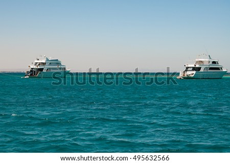 few white yacht near coral reef in the calm blue sea blue cloudless sky