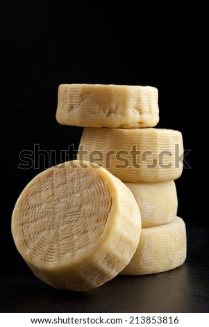 few whole forms of cheese parmesan, one atop the other. on black. italian pecorino - stock photo