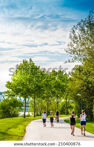Few women running and cycling in beautiful green park alongside the river.Captured at Danube island,Vienna,Austria - stock photo