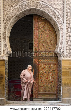 FEZ, MOROCCO - APRIL 19: Unkown woman going out from mosque, traditional morocco door in backgroun in April 19, 2015. - stock photo