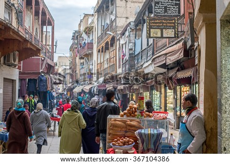 Fez, Morocco - December 14, 2015: Moroccan citizens in a relaxation quotidian scene in Bab Mahrouk at sunset, view from Bou Jeloud square. Bab Mahrouk is a gate to ancient Fez El Bali Medina. Morocco. - stock photo