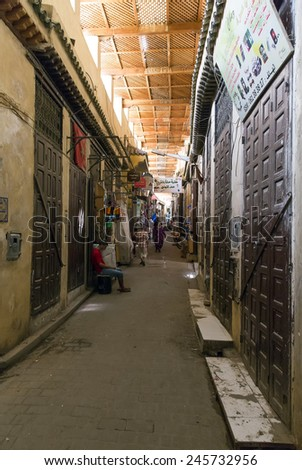 FEZ, MOROCCO - JULY 19: People in a souk on July 19, 2014 in Fez, Morocco. The medina is listed as a UNESCO World Heritage Site and is believed to be one of the world's largest car-free urban areas. - stock photo