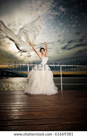 Fiance in the wind. Pretty lady in a wedding dress on deck. - stock photo