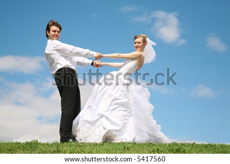 fiance with the bride they hold each other for the hands on to the meadow 2
