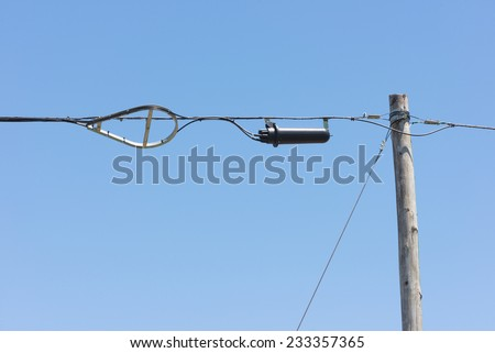 Fiber optic splice enclosure and cable storage bracket hanging on aerial messenger strand bonded to a wood pole