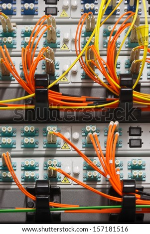 Fiber optics cables plugged in to high speed switch with one port free  - stock photo