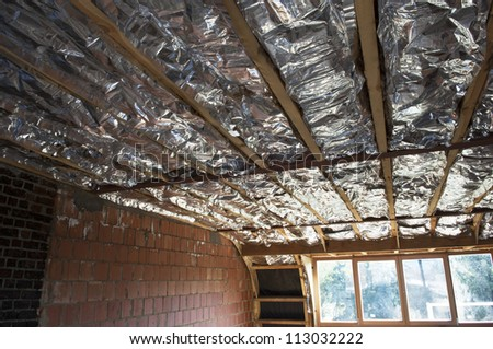 Fiberglass insulation installed in the sloping ceiling of a house. - stock photo