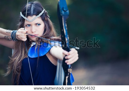 fictional forest hunter girl with bow and arrow - stock photo