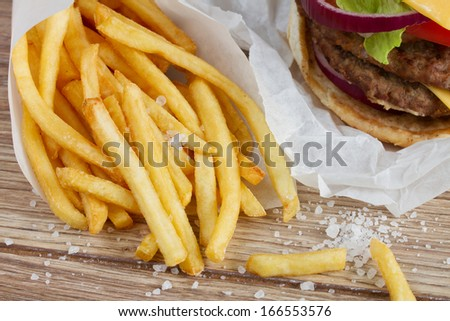 fied potato french fries with salt on wooden table - stock photo