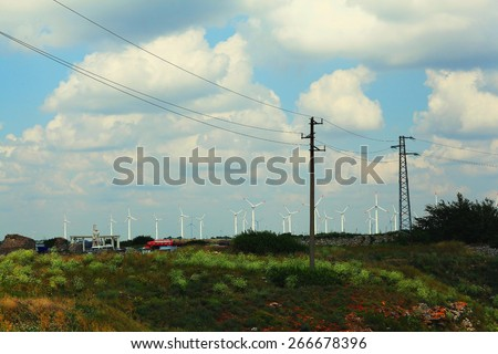 field landscape wire power lines windmills - stock photo