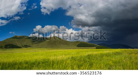Field landscape with dramatic sky