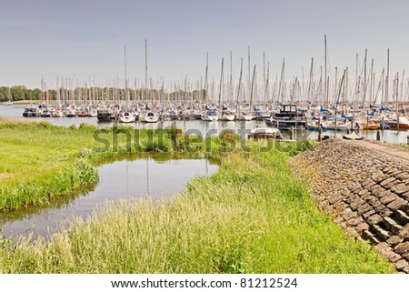 Field of grass with little pond and harbour in the background on hot summer day with blue sky. Old dutch town, Enkhuizen, the Netherlands. - stock photo