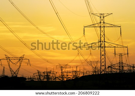 field of high voltage towers under dramatic sky - stock photo