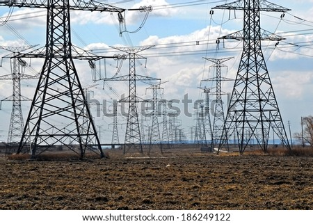 Field of many electrical transmission towers against cloudy sky. - stock photo