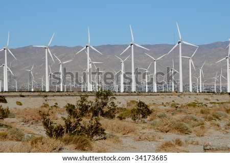 field of wind turbines in the desert against blue sky - stock photo