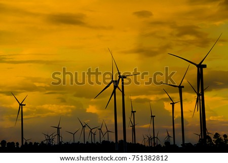 Field of wind turbines with orange sky. In the evening