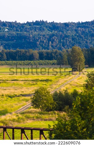 Field road, being like across a large green meadow with grass and trees on the background of a hill with forest. Excellent panoramic landscape with the vision and the amount of space. - stock photo