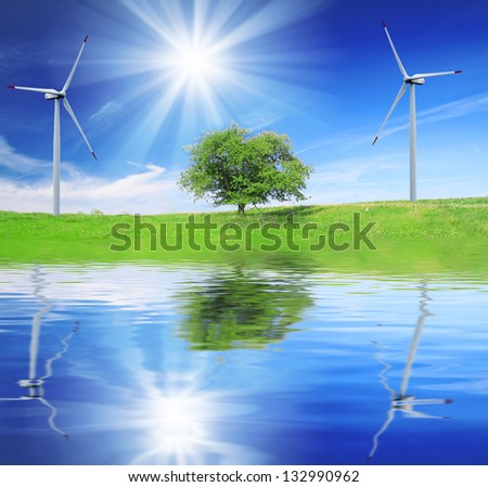 Field, tree and blue sky with wind turbines and reflection in water - stock photo