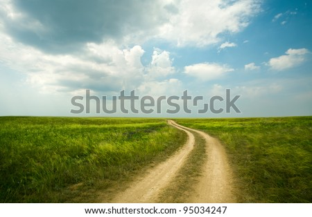 Field winding road through the green meadow - stock photo