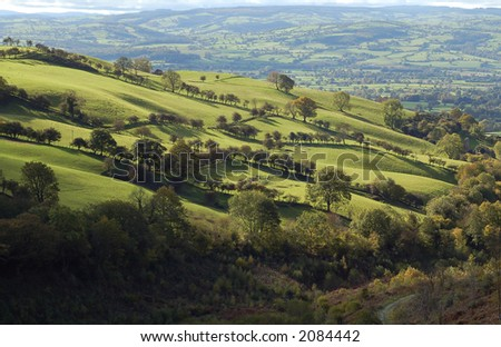 Fields and pastures as far as the eye can see viewed from the top of a hill in Wales