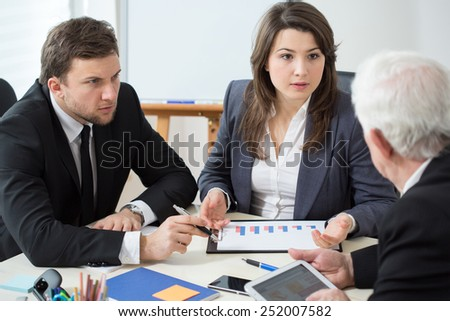 Fierce discussion between three elegant businesspeople - stock photo