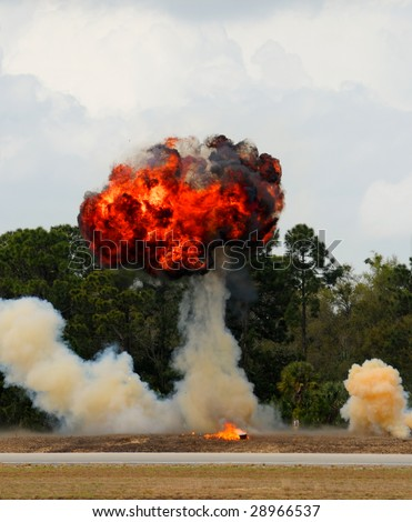 Fiery explosion in field near forested area - stock photo