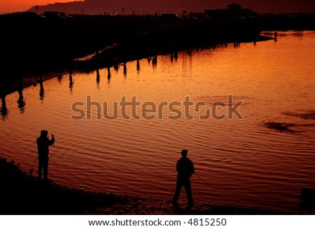 Fiery northern sunset over Homer, Alaska is reflected in the choppy waters, and jumping salmon (Oncorhynchus kisutch), of fishing hole on the spit. - stock photo