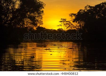 Fiery orange sunset on an Amazon tributary in Peru - stock photo