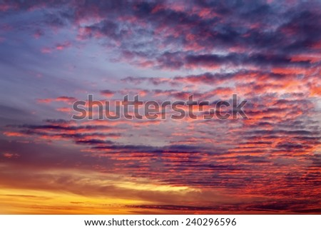 Fiery orange sunset sky. Beautiful sky. Clouds in motion in the sky during sunset  - stock photo