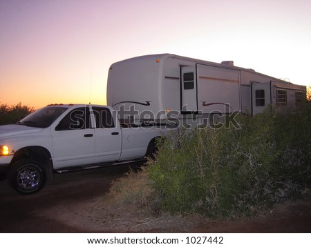 fifth wheel travelling trailer at sunset - stock photo