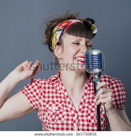 fifties singer in studio - fun young female rocker with retro style snapping her fingers for rhythm, singing in old fashioned micro, gray background - stock photo