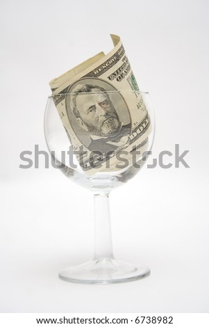 Fifty dollar bills in the glass for wine isolated on light gray