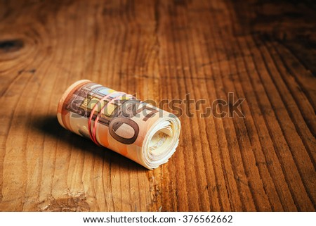 Fifty euro banknotes rolled up with rubber band as home savings - stock photo