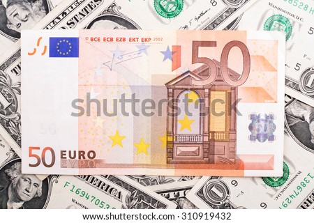Fifty euro bill over dollars background - stock photo
