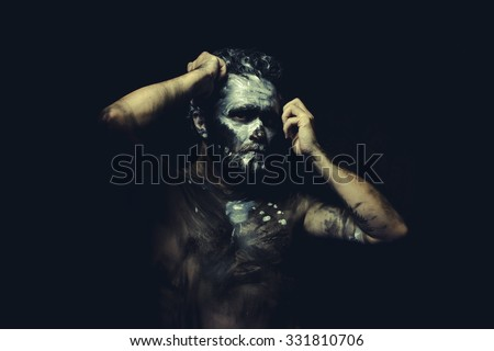Fight, wild man with white painted face and full body black paint - stock photo