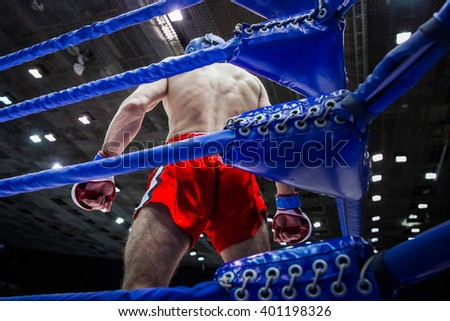 fighter boxer in corner of ring before fight on competitions in mixed fighting single combats - stock photo