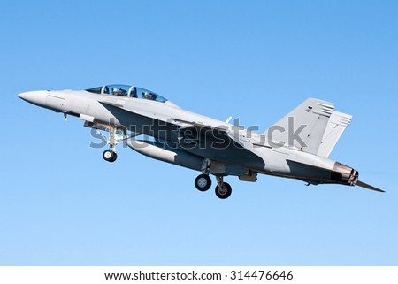 Fighter jet climbing into the blue sky - stock photo