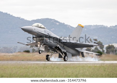 Fighter jet touches down on the runway with a plume of tyre smoke - stock photo