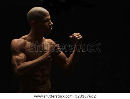 Fighter, low-key lighting - stock photo