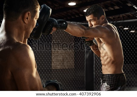 Fighter training his boxing skills in octagon - stock photo